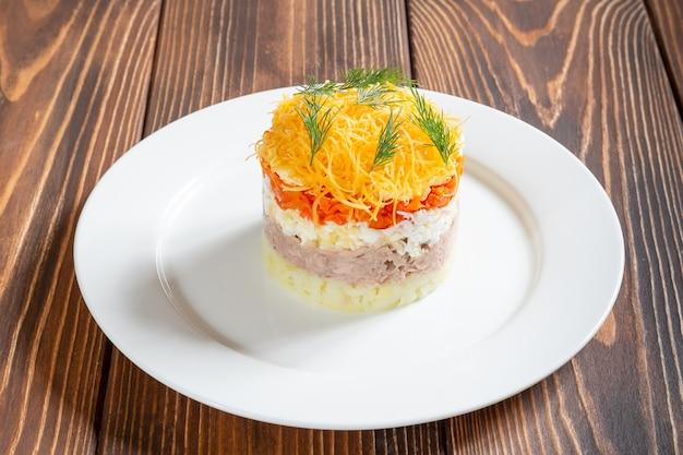 Plaat van traditionele russische salade mimosa met vis