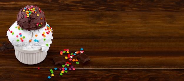 Plaat van vanille en en chocolade-ijs scoop swith hagelslag en wafelkegels op houten