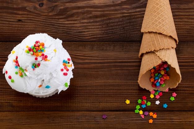 Plaat van vanille-ijs scoop swith hagelslag en wafel kegels op houten achtergrond met kopie ruimte.