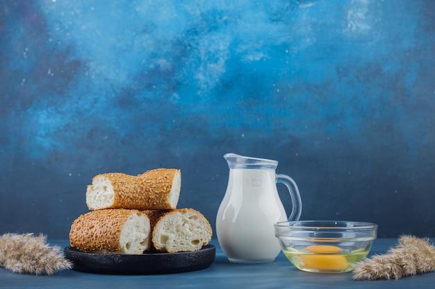 Plaat van vers gebak met glas melk en eigeel op blauwe ondergrond.