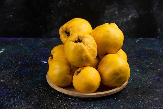 Plaat van vers kweepeer fruit op donkere tafel geplaatst.