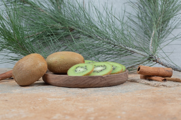 Plaat van verse kiwi en pijpjes kaneel op marmeren lijst.