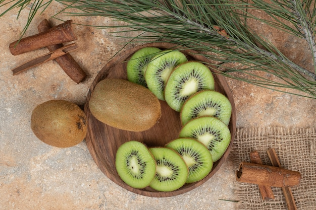 Plaat van verse kiwi en pijpjes kaneel op marmeren oppervlakte.