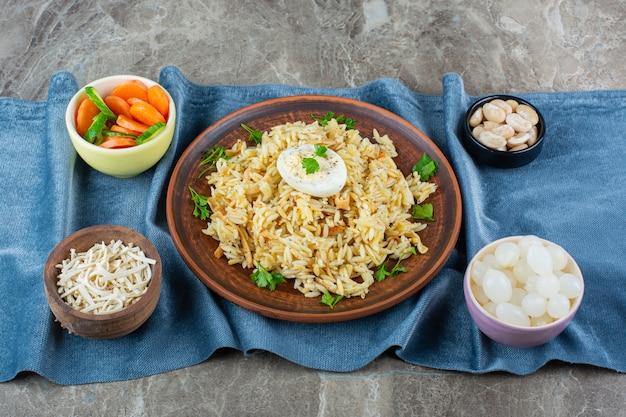 Plaat van verse macaroni en eieren op marmeren oppervlak.