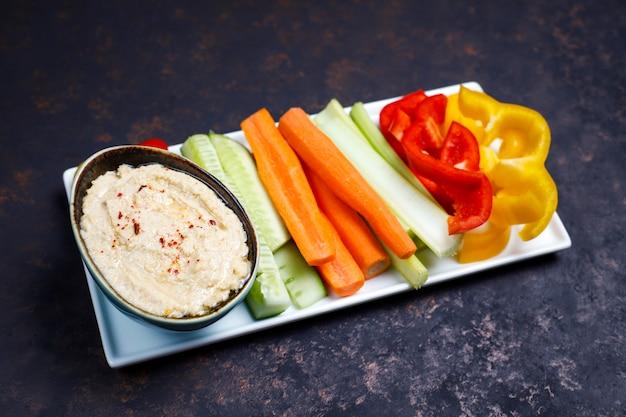 Plaat van verse organische groentensalade met hummus op donkere bruine of concrete oppervlakte