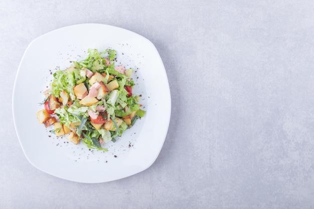 Plaat van verse salade met worstjes op stenen achtergrond.