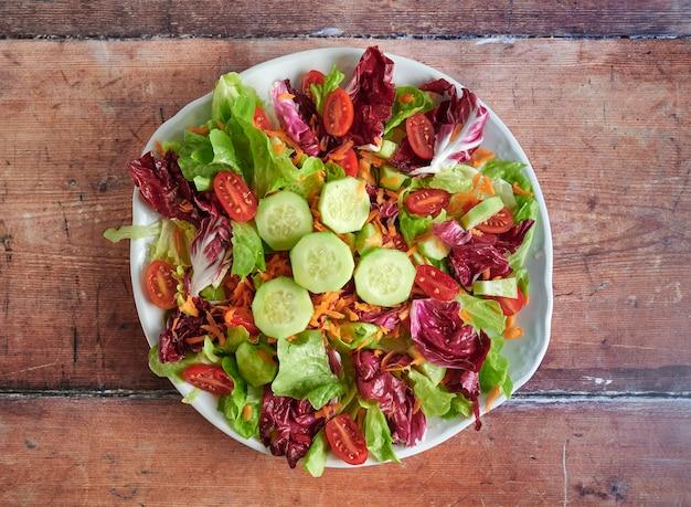 Plaat van verse salade op houten.