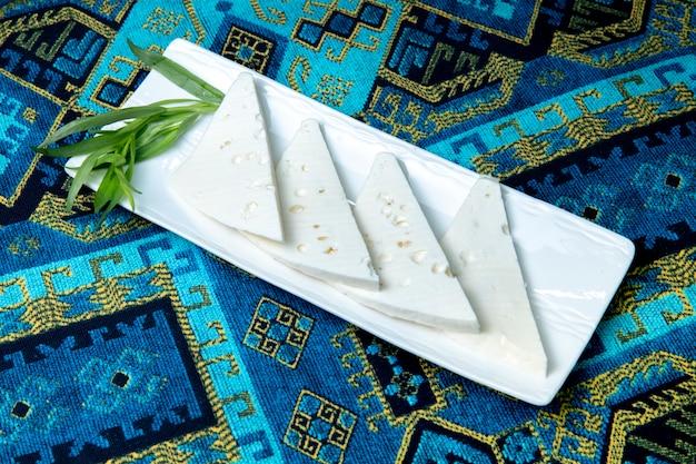 Plaat van witte kaas geserveerd met greens