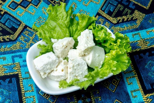 Plaat van witte kaas met sla