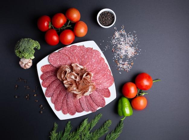 Plaat van worst en vlees, op zwart met tomaten, dille, knoflook en broccoli