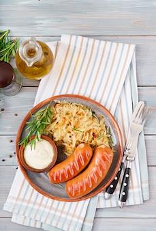 Plaat van worsten en zuurkool op houten lijst. traditioneel oktoberfest-menu. plat leggen. bovenaanzicht