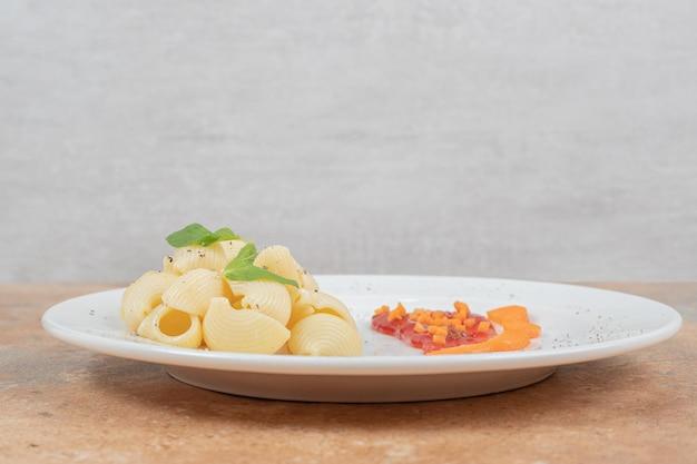 Plaat van zeeschelpvormige pasta met saus op marmeren ruimte.