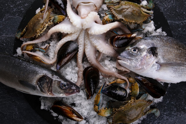 Plaat van zeevruchten met verse inktvis, mosselen, blauwe krab, zeebaars en doradovissen,