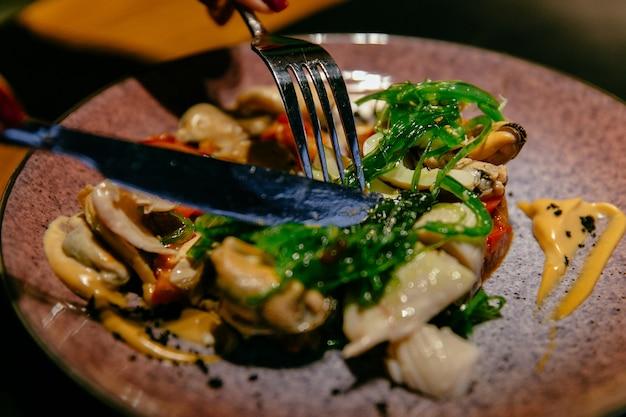 Plaat van zeevruchtensalade met saus. vork en mes. voedsel concept.
