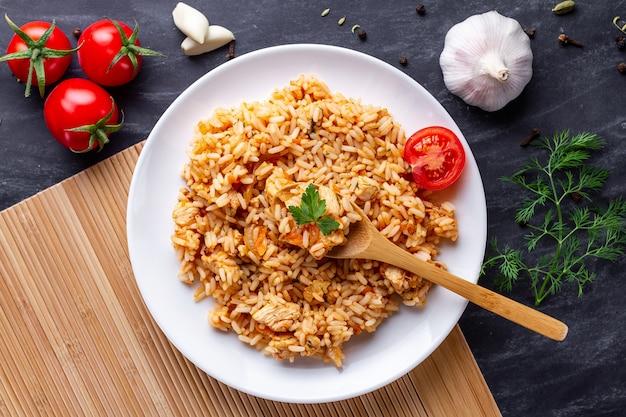 Plaat van zelfgemaakte heerlijke pilaf met kip, verse peterselie en rijpe groenten voor de lunch