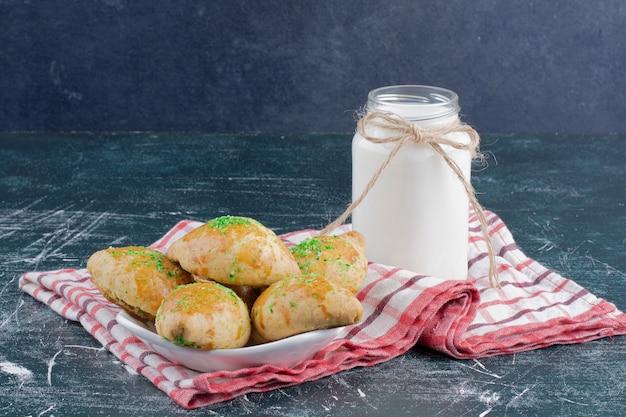 Plaat van zelfgemaakte koekjes en kruik melk op marmeren tafel.