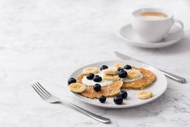 Plaat van zelfgemaakte ontbijt met bosvruchten en kopje koffie aan marmeren tafel.