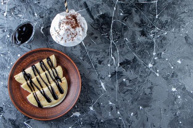 Plaat van zelfgemaakte pannenkoeken met chocolade topping en glas koffie.