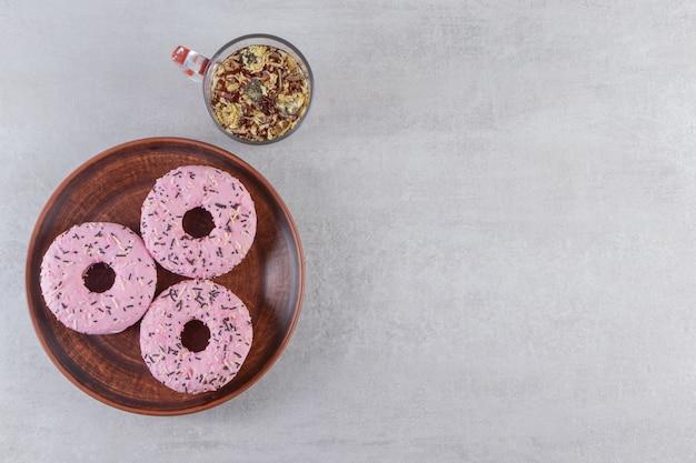 Plaat van zoete roze donuts met kop hete thee op stenen tafel.