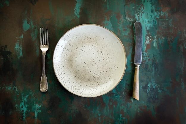 Plaat, vork en mes op een roestige metalen tafel
