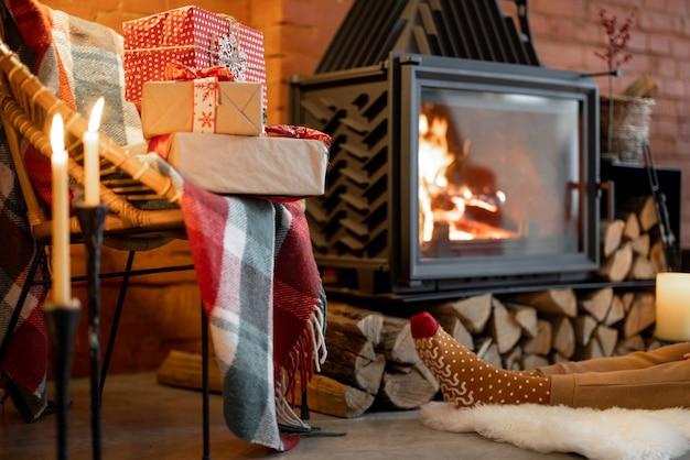 Plaats bij een brandende open haard versierd met een nieuwjaarscadeautje in gezellig interieur