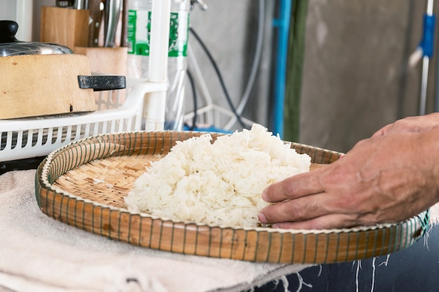 Plaats de gestoomde kleefrijst op een bamboe dienblad om de warmte te verspreiden