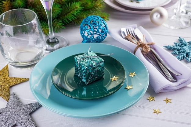 Plaats de tafel instelling voor kerstmis witte tafel met paarse decor elementen met groene takken kerstboom