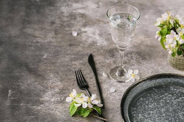 Plaats de tafel met bloeiende appelboomtakken en bloemen