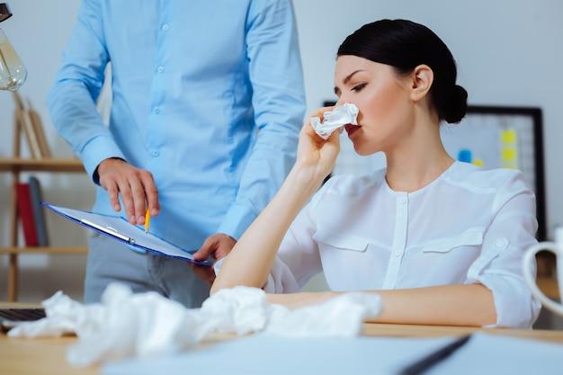 Plaats het hier. attente brunette vrouw haar hoofd draaien en neus afvegen terwijl ze haar teken op document gaat zetten