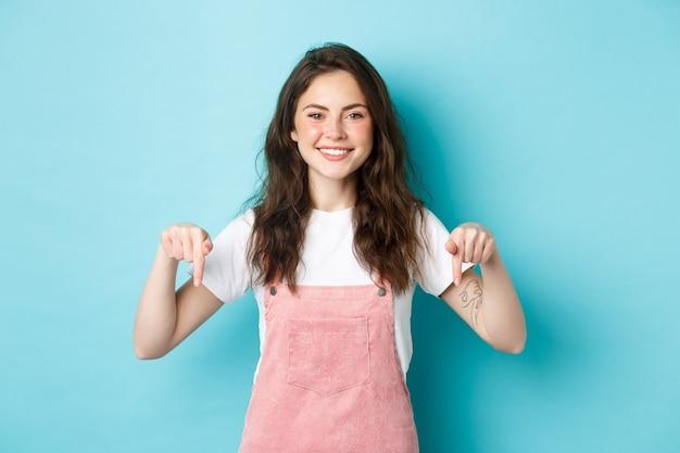 Plaats hier uw logo. vrolijke brunette vrouw die met de vingers naar beneden wijst en naar de camera glimlacht, product aanbeveelt, verkooppromo-aanbieding toont, staande tegen een blauwe achtergrond.