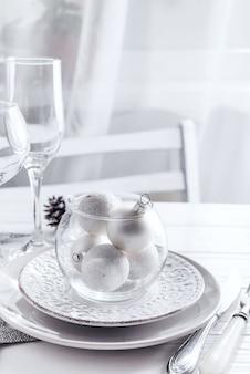 Plaats tabel instelling op witte tafel met kerst decor elementen. zilvere kleur