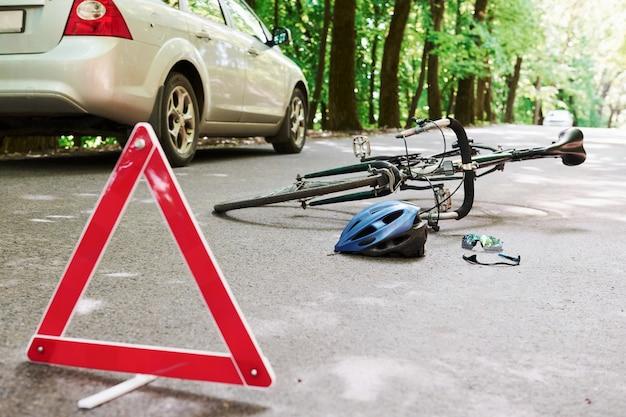 Plaats van ramp. fiets- en zilverkleurig auto-ongeluk op de weg bij bos overdag