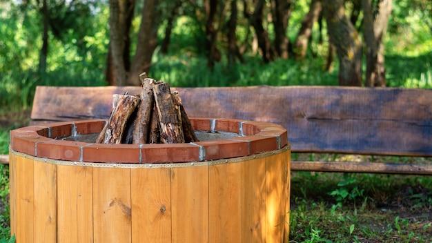 Plaats voor kampvuur met houten bank bij glamping. groen rondom