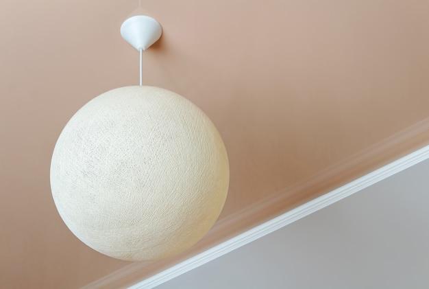 Plafondlamp in de vorm van een rieten bol. minimalistisch kamerinterieur.