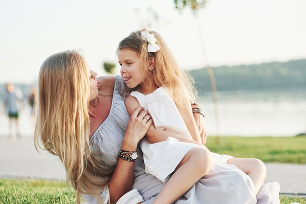 Plagen. foto van jonge moeder en haar dochter die goede tijd hebben op het groene gras met meer bij achtergrond.