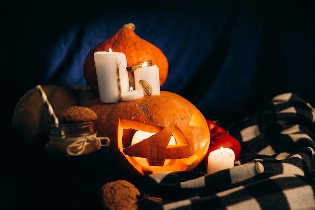 Plaid ligt rond halloween-pumpking met glanzende kaarsen eromheen en een kop warme chocolademelk met koekjes