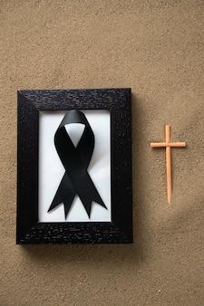 Plak kruis met fotolijst op het zand