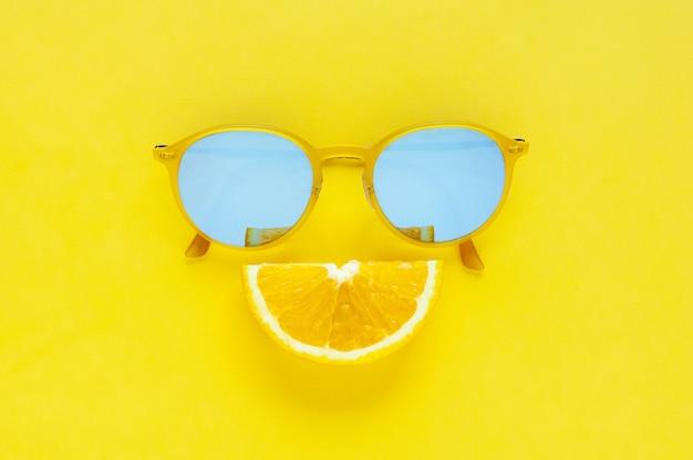 Plak oranje fruitreeksen als glimlachmond en gele zonnebril op gele achtergrond.