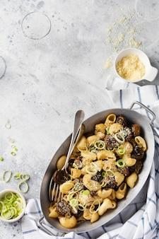 Plak pipa rigate en champignons champignon gebakken in sojasaus, met peper, parmezaanse kaas en gestoomde uien in een oude metalen kom op een oude vintage tafel