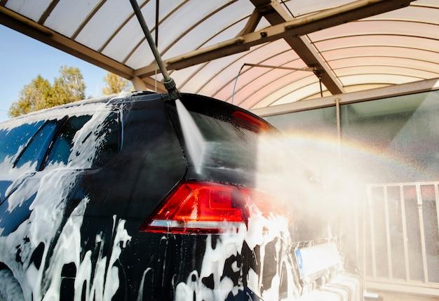 Plak spuitwater op een auto bedekt met schuim