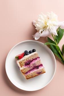 Plak van bosbessencake op witte plaat en pioenbloem