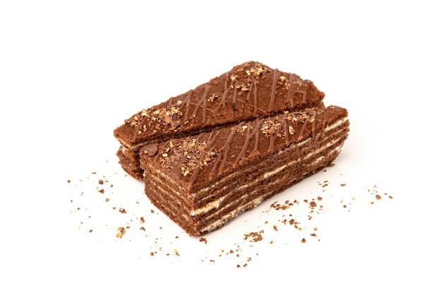 Plak van chocoladetaart met melkvulling en chocolade die op wit wordt geïsoleerd.