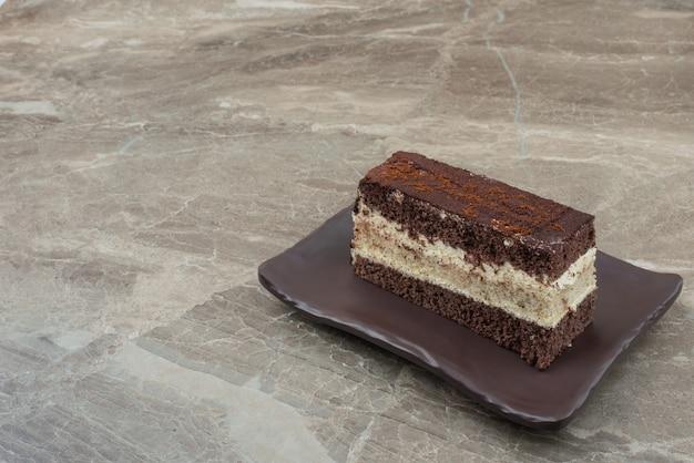 Plak van chocoladetaart op zwarte plaat.