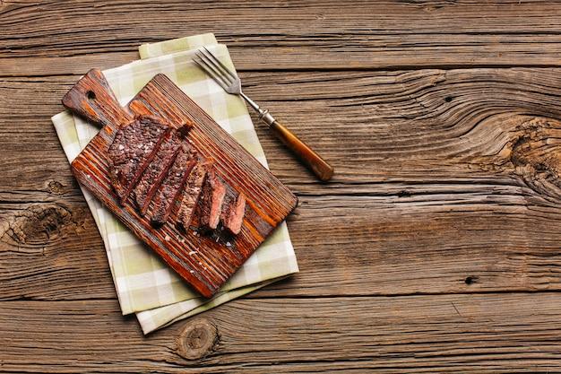 Plak van geroosterd lapje vlees op scherpe raad met vork en servet over lijst