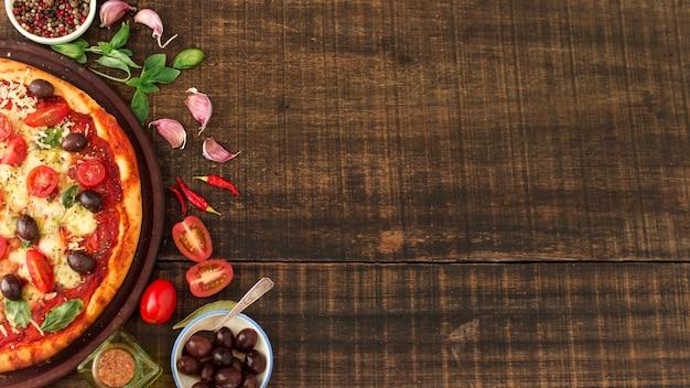 Plak van heerlijke pizza met ingrediënten op geweven houten achtergrond