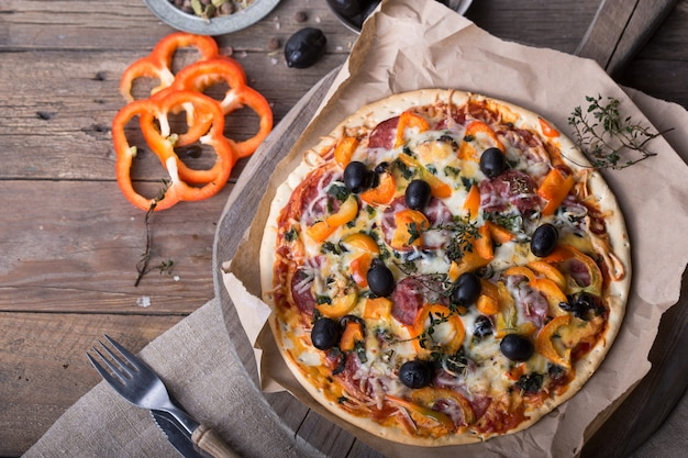 Plak van pepperoni pizza. handen plukken pizzapunt. bovenaanzicht van smakelijke hete pepperoni pizza op zwarte betonnen achtergrond