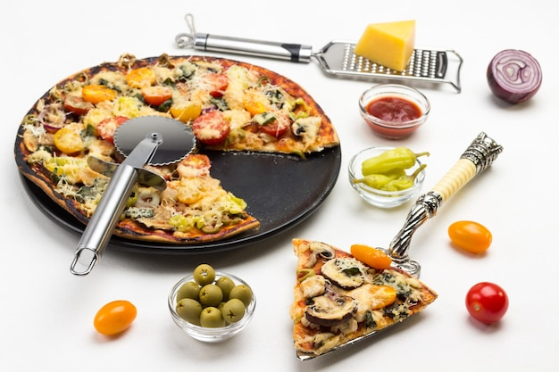 Plak van pizza op lepel en pizza op zwarte plaat