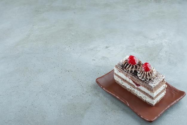 Plak van smakelijke cake op bruine plaat.