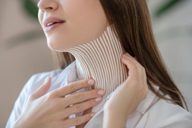 Plakband. jonge vrouw banden op haar nekspier zetten en glimlachen