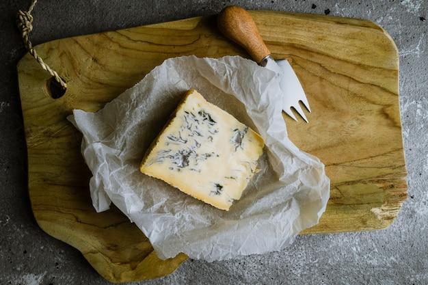 Plakje blauwe kaas op een houten bord met kaasmes